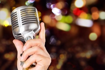 Female hand holding a single retro microphone - isolated image