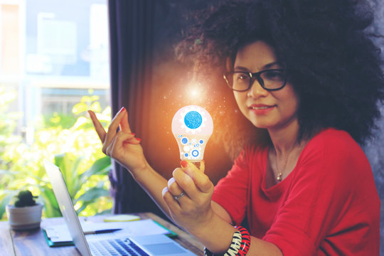 Creative idea and innovation concept, Businesswoman hand holding light bulb with hologram in home office