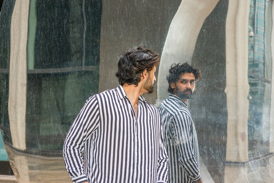 Raining day - grainy, drizzling, wet feel. Young East Indian American Man in New York, with beard, wearing black, white striped shirt, standing outside, turning around, looking reflection on mirror..