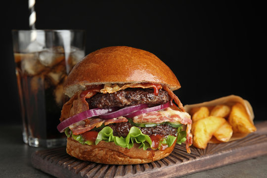 Tasty burger with bacon and fried potatoes served on table