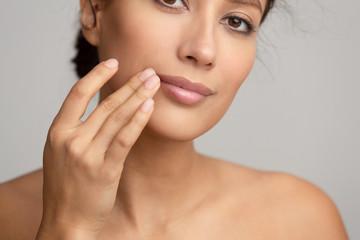 Obraz Natural beauty. Woman applying balsam, touching lips - fototapety do salonu
