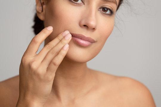 Natural beauty. Woman applying balsam, touching lips