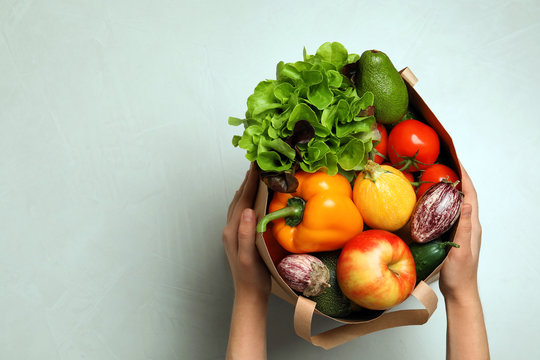 Woman holding paper bag with fresh vegetables and fruits on light background, top view. Space for text