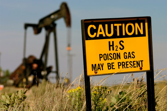 Hobbs, New Mexico, United States.  Poison gas sign with oil derrick.