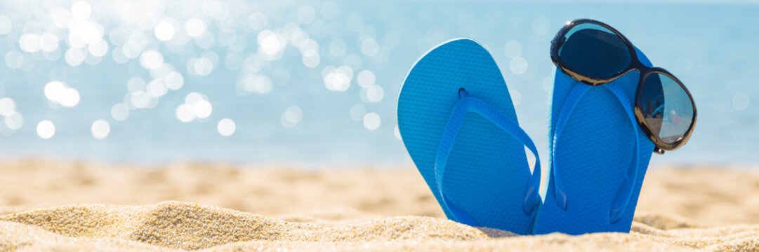 flip flops with sun glasses on sunny tropical Caribbean beach, turquoise waters on caribbean island, hot summer day vacation