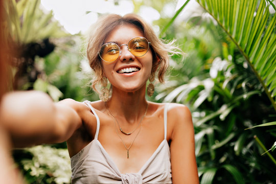 Young caucasian pretty woman wearing yellow round glasses making selfie with happy smile on background exotic plants