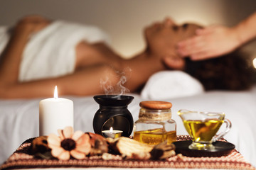 African woman having face massage, relaxing in spa salon
