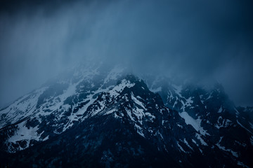 Misty fog covered snowy mountain of the Sierra Nevada range. This moody capture shows the dark and majestic aura of the tall mountain peaks found in Eastern California near Mammoth Lake Wall mural