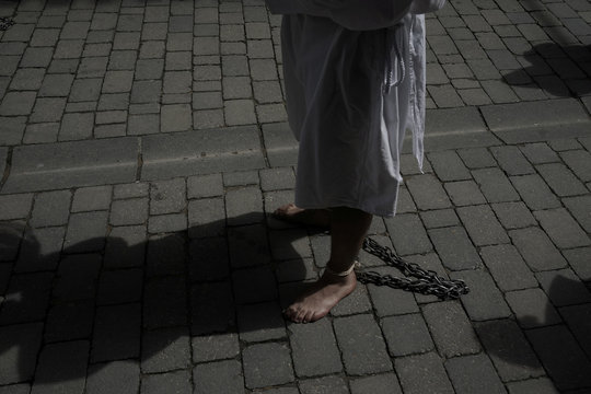 """A penitent from the Santa Vera Cruz brotherhood, known as """"Los Picaos"""", walks with his feet chained during Good Friday celebrations in San Vicente de la Sonsierra"""