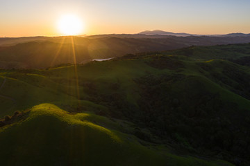 A beautiful dawn breaks over the green hills in Northern California. A wet winter has caused lush vegetation growth in the East Bay hills near San Francisco.