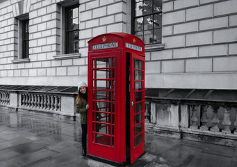 Young girl next to a telephone booth in London