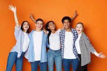 Students having fun over orange studio background
