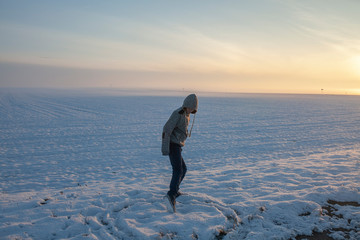 the guy draws a circle with his feet, in the winter in a snowy field