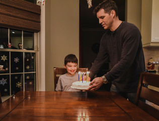 Young boy smiling as dad puts his birthday cake in front of him.