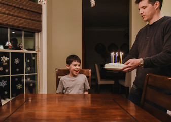 Young boy smiling as dad brings his birthday cake with candles to him.