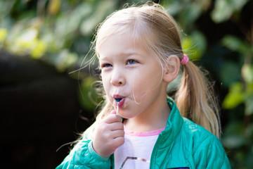 blond girl sucking on lollipop outdoors