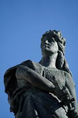Frauenstatue mit Schwert vor blauem Himme