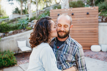 Side view of wife kissing husband while standing in yard