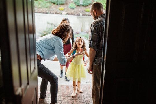 parents looking at daughter leaving for school seen through doorway