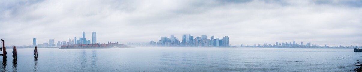 Panoramic New York City skyline with dramatic low clouds including Jersey City, Manhattan, and Brooklyn as seen from Liberty Island