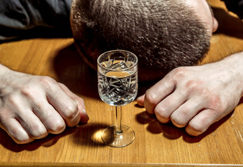The man fell asleep drunk at the table in front of a glass of vodka