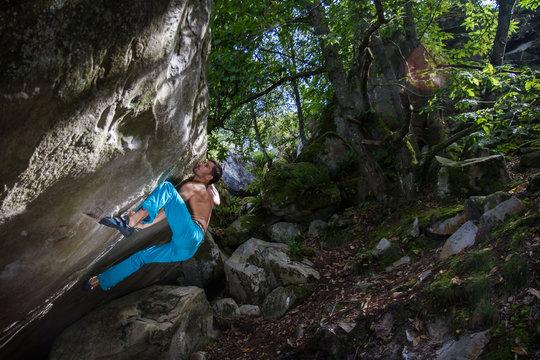 Jeune homme avec le dos musclé qui escalade un rocher en forêt torse-nu, déterminé, en pleine effort de grimpe intense