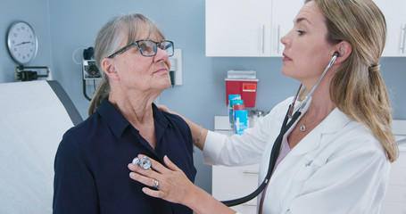 Female doctor using stethoscope listening to senior patients heart. Older woman visiting her primary care physician for a regular check up