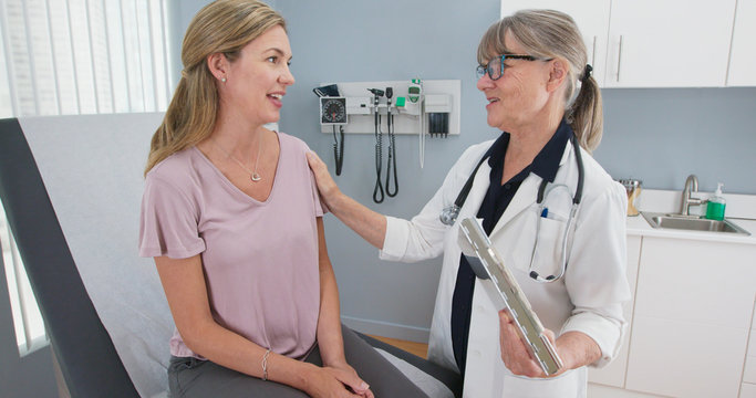 Two shot of woman talking to her reassuring primary care doctor in exam room. Middle aged patient having appointment with female senior physician