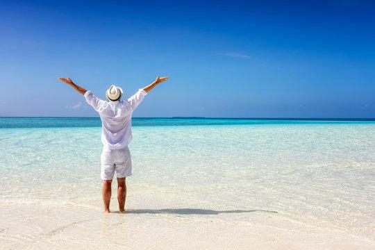 Mann in weißer Sommerkleidung steht am tropisch Strand und genießt die Freiheit