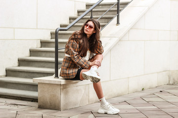 Portrait shooting of a stylish girl. Beige shades. Trends of spring and summer 2019. Wide jacket and belt leather bag. White sneakers and bike shorts Wall mural