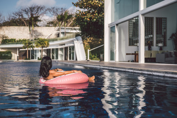 portrait of a sexy woman relaxing in a big pool on an inflatable pink donut