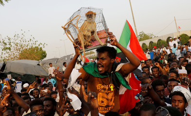 A Sudanese protester holds a monkey, that represents former Sudanese President Omar al-Bashir, in a cage wrapped by ropeÊas he demands capital punishment for him, during a demonstration in front of the Defence Ministry in Khartoum