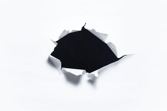 Dark torn hole in white paper.