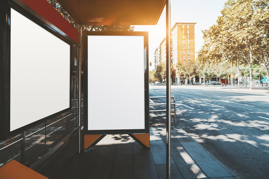 A template of blank ad posters inside of a bus stop; vertical and horizontal information banner mock-ups placeholders in a stop of public transport with the road near; empty outdoor billboards mockups