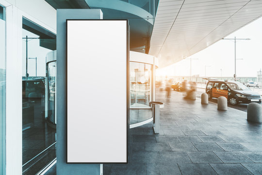 A blank narrow vertical poster mock-up near the entrance of a modern airport terminal with taxis and silhouettes of passengers; an empty info billboard template near railway station depot or a mall