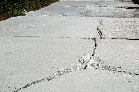 Crack in concrete slab of coastal promenade as result of sea water erosion