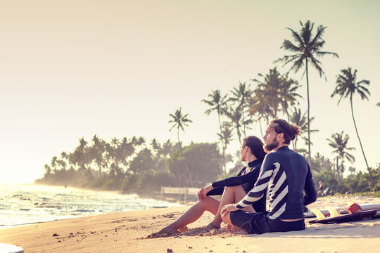 Young beautiful loving couple friends are sitting on the sand by the ocean with surfboards and watching sports active lifestyle holidays honeymoon...