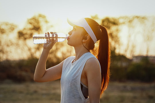 Young woman runner wears white sport vest, white cap, black short pants drinks mineral water after running.