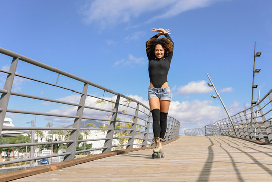 Afro hairstyle woman on roller skates riding outdoors on urban bridge