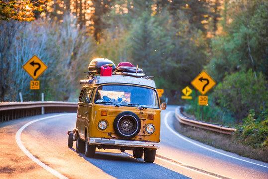 Old mini van for tourist travels rushing along sunny winding road