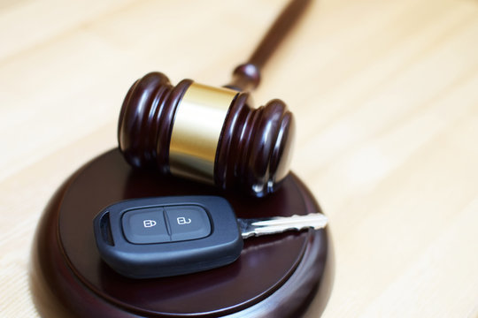 Judges gavel, sounding block and car key on light wooden background with copy space. Car auction, legal trial of traffic accident, traffic law and justice concept.