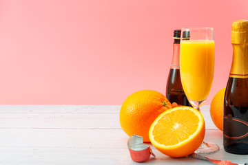 Lush mix drink, summer alcoholic beverages and refreshing mimosa cocktail concept with oranges, champagne flute and bottles of bubbly isolated on white wooden table and pink background with copy space