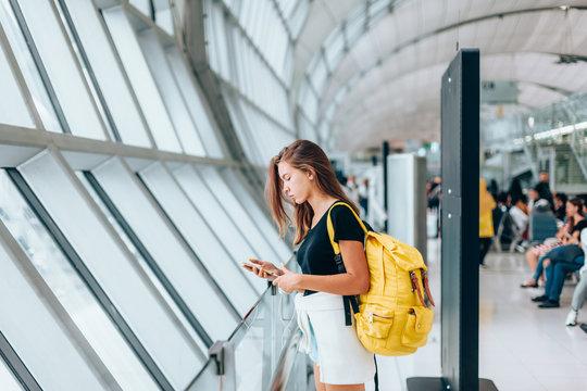 Teen girl waiting for international flight in airport departure terminal