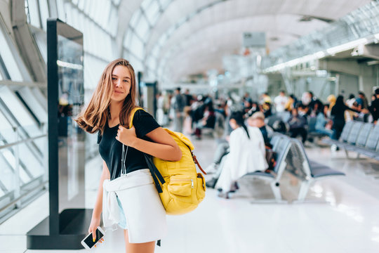 Teen girl waiting for international flight in airport departure terminal