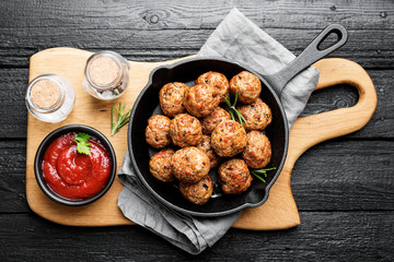 Meatballs served with tomato sauce in frying pan .