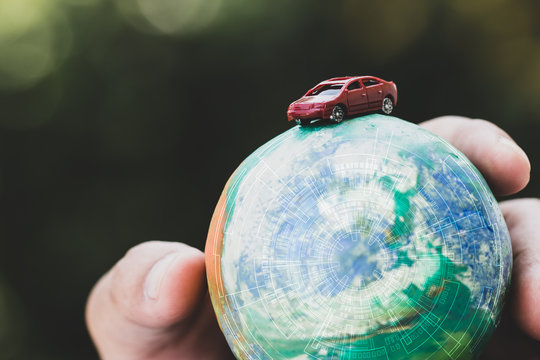 Eco friendly Save world concept. Red car and Hands holding Model globe clay with radar Natural background. Ideas of earth maintenance by reducing energy consumption, Travel around the world