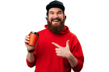 Photo of bearded guy standing over white background, pointing at orange cup and looking at camera