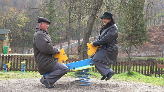 Grandparents couple having fun at child playground, smiling laughing in nature