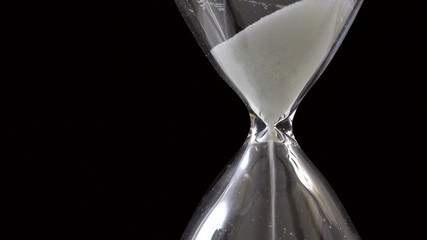 Detail of sand pouring in hourglass on black background, time passing concept