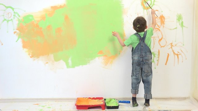 Little artist painting white wall, amusing child have fun
